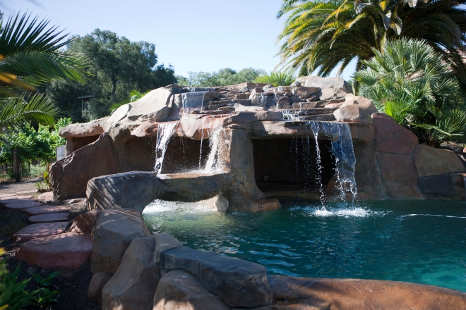This is a great swimming pool with amazing clients. Walkout beach, waterfalls, caves, spa, grotto, vanishing edge, rock decking and pebble tec pool plaster.
